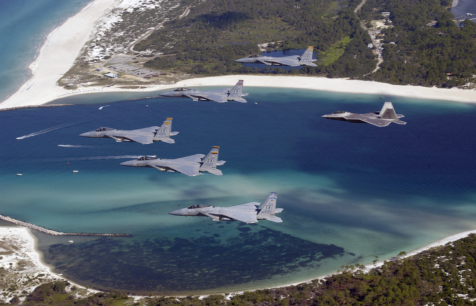 US Air Force (USAF) Brigadier General (BGEN) Larry New, Commander of the 325th Fighter Wing (FW), Air Education and Training Command (AETC) located at Tyndall Air Force Base (AFB), Florida (FL), leads a formation of four F-15C Eagle fighters from the 1ST, 2nd, and 95th Fighter Squadron's (FS) and one F/A-22 Raptor (right) from the 43rd FS, each flown by their respective Squadron Commander