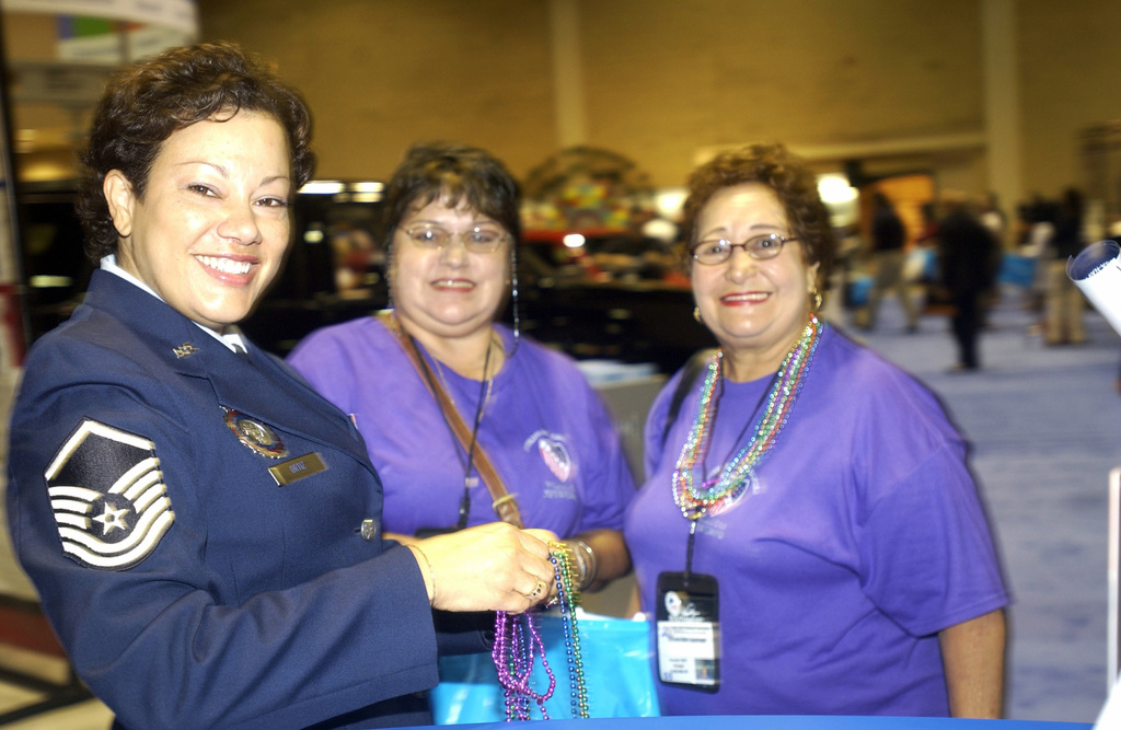 US Air Force (USAF) MASTER Sergeant (MSGT) Heidi Ortiz In-service Recruiter from Langley Air Force Base (AFB), Virginia (VA), hands beads to Puerto Rico Delegates Carmen Aida Lopategui and Argelia Mercedes Marrero from Truillo Alto, Puerto Rico (PR), during the League of United Latin American Citizens (LULAC) at the 75th Annual National Convention and Exposition at the Henry B. Gonzalez Convention Center in San Antonio, Texas (TX)