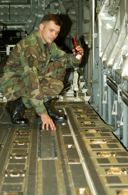 US Air Force (USAF) MASTER Sergeant (MSGT) Marvin Hitt, 446th Maintenance Squadron (MXS), inspects the 25,000 pound tie down rings on a C-17 Globemaster III cargo aircraft during a routine maintenance check of the aircraft on McChord Air Force Base (AFB), Washington (WA)