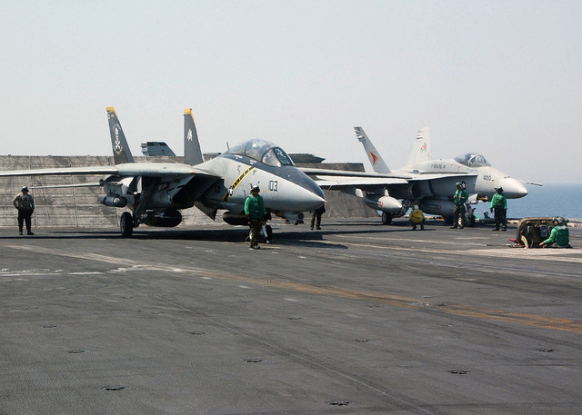 A US Navy (USN) F-14D Tomcat, Fighter Squadron 103 (VF-103), Jolly Rogers, Naval Air Station (NAS) Oceana, Virginia (VA), and a USN F/A-18C Hornet, Strike Fighter Squadron 81 (VFA-81), Sunliners, NAS Oceana, make final preparations for launch onboard the Aircraft Carrier USS JOHN F. KENNEDY (CV 67), on the Persian Gulf. JFK and Carrier Air Wing 17 (CVW-17) are participating in SUMMER PULSE 2004, the simultaneous deployment of seven carrier strike groups (CSG), demonstrating the ability of the Navy to provide credible combat forces across the globe, in five theaters with other US, allied, and coalition military forces. SUMMER PULSE is the Navy's first deployment under its new Fleet...