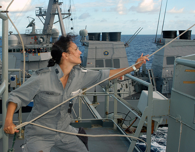 Royal Australian Navy (RAN) Able SEAMAN, Communications SPECIALIST, Natalie Haumu, retrieves a signal flag, aboard the RAN DURANCE CLASS: Underway Replenishment Tanker, Her Majestys Australian Ship (HMAS) SUCCESS (OR 304), as the ship begins a Refuel At Sea (RAS) operation with the US Navy (USN) ARLEIGH BURKE CLASS: (Flight I), Guided Missile Destroyer, USS JOHN PAUL JONES (DDG 53) (underway background), while participating in Exercise RIMPAC 2004. RIMPAC is the largest international maritime exercise conducted in the waters around the Hawaiian Islands, and is designed to enhance the tactical proficiency of participating units in a wide array of combined operations at sea, while...