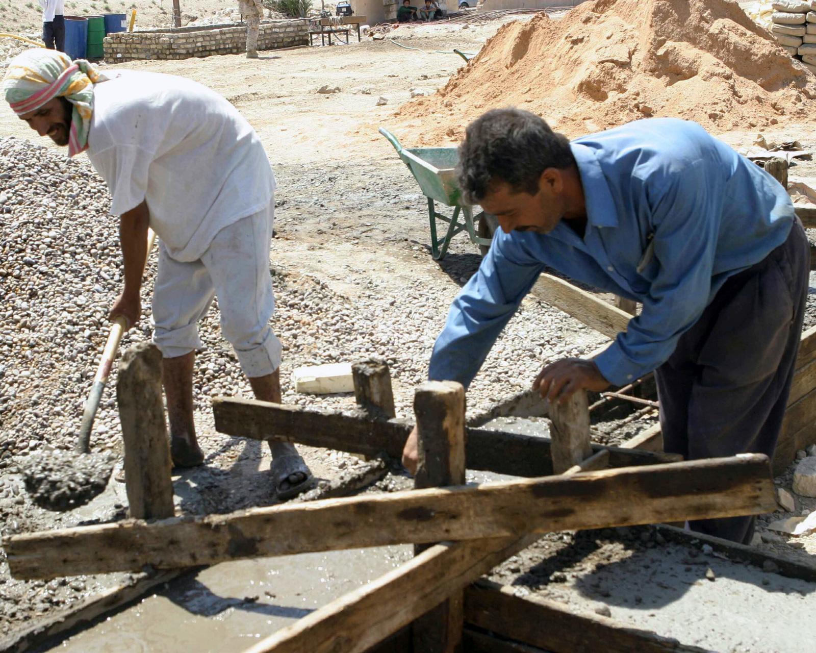 Two local Iraqi civilian contractors work on building a