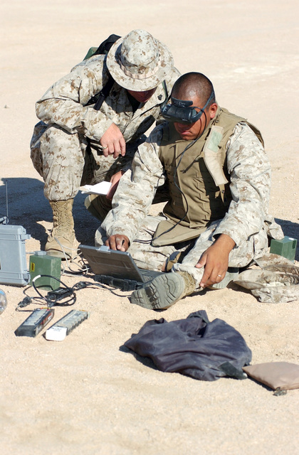 US Marine Corps (USMC) Marine Serget (SGT) William Hartzfeld (left), with the Marine Corps Systems Commd (MCSC), observes USMC Marine Private First Class (PFC) Germond Patton, assigned to the 3rd Light Armored Reconnaissce Battalion (LARB), view the ground monitor of a Dragon Eye Unmned Aerial Vehicle (UAV) in flight during training at the Marine Corps Air Ground Combat Center (MCAGCC), Marine Air Ground Task Force Training Center (MAGTFTC), Twentynine Palms, California (CA). The Dragon Eye is a five-lbs., back-packable, modular unmned aerial vehicle guided by computers that provides real time video of the terrain below it. The equipment provides USMC small units surveillce...