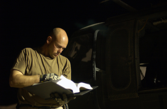 US Army (USA) Sergeant (SGT) Joseph Candiloro, a UH-60 Black Hawk helicopter Mechanic assigned to the 45th Medical Company refers to the Technical Operations (TO) manual as he works on the aircrafts oil cooler at Camp Cooke, Iraq, during Operation IRAQI FREEDOM