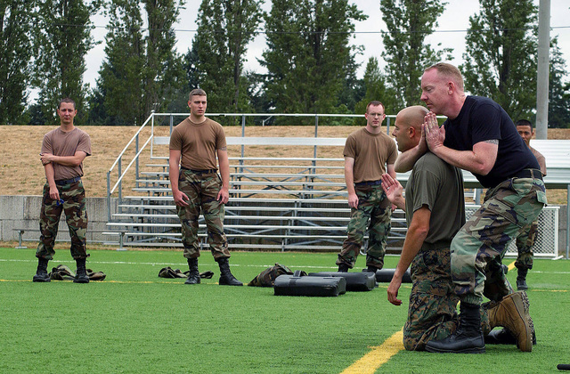 US Marine Corps (USMC) STAFF Sergeant (SSGT) Jeffery Cassell (on knees), prepares to tap out of a chokehold initiated by US Air Force (USAF) Technical Sergeant (TSGT) John Foley, during training at McChord Air Force Base (AFB), Washington (WA)