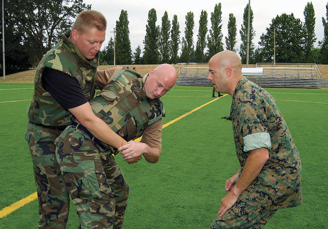 US Marine Corps (USMC) STAFF Sergeant (SSGT) Jeffery Cassell (right), gives pointers to US Air Force (USAF) STAFF Sergeant (SSGT) Jason Van Winkle and USAF SSGT Ray Taylor, both from the 62nd Aerial Port Squadron (APS), on the correct way to do a throw at McChord Air Force Base (AFB), Washington (WA)