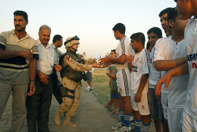 US Army (USA) Lieutenant Colonel (LTC) Kim Myran (center), 425th Civil Affairs Battalion (CAB), 82nd Field Artillery Regiment (FA), 1ST Cavalry Division (CAV), distributes soccer balls during the inaugural soccer game on a newly built soccer field in downtown Baghdad, Baghdad Province, Iraq (IRQ), during Operation IRAQI FREEDOM. The opening of the new soccer field was a combined effort by local Iraqis, the Iraqi Ministry of Youth, and Coalition forces