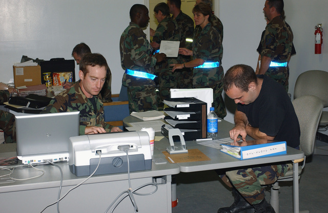 Massachusetts Air National Guard (MAANG) Lieutenant (LT) Sampson (seated right), 102nd Fighter Wing (FW), goes through the processing line in Building (BLDG) 155 during a 102nd FW Operational Readiness Exercise (ORE) at Otis Air National Guard Base (ANGB), Massachusetts (MA)