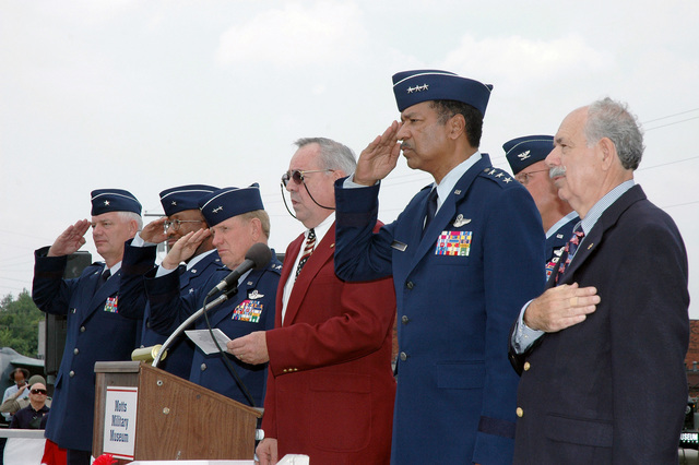 These distinguished guests (Left to Right): Ohio Air National Guard (OHANG) Brigadier General (BGEN) Richard Green, Assistant Adjutant General (AG) for Air and Commander, OHANG; US Air Force (USAF) BGEN Vergel Lattimore, Chaplain and Air National Guard (ANG) assistant to the Air Force CHIEF of Chaplains; OHANG Major General (MGEN) John Smith, AG Ohio National Guard, Joint Force Headquarters (JF HQ); Mr. Jan Maroscher (singing the US National Anthem); USAF Lieutenant General (LGEN) Daniel James, III, Director of the US ANG; USAF (ret.) Colonel (COL) Ronald Albers (partially hidden); and Mr. Warren Motts, Director, Motts Military Museum, stand at attention and salute as the OHANG 121 Air...
