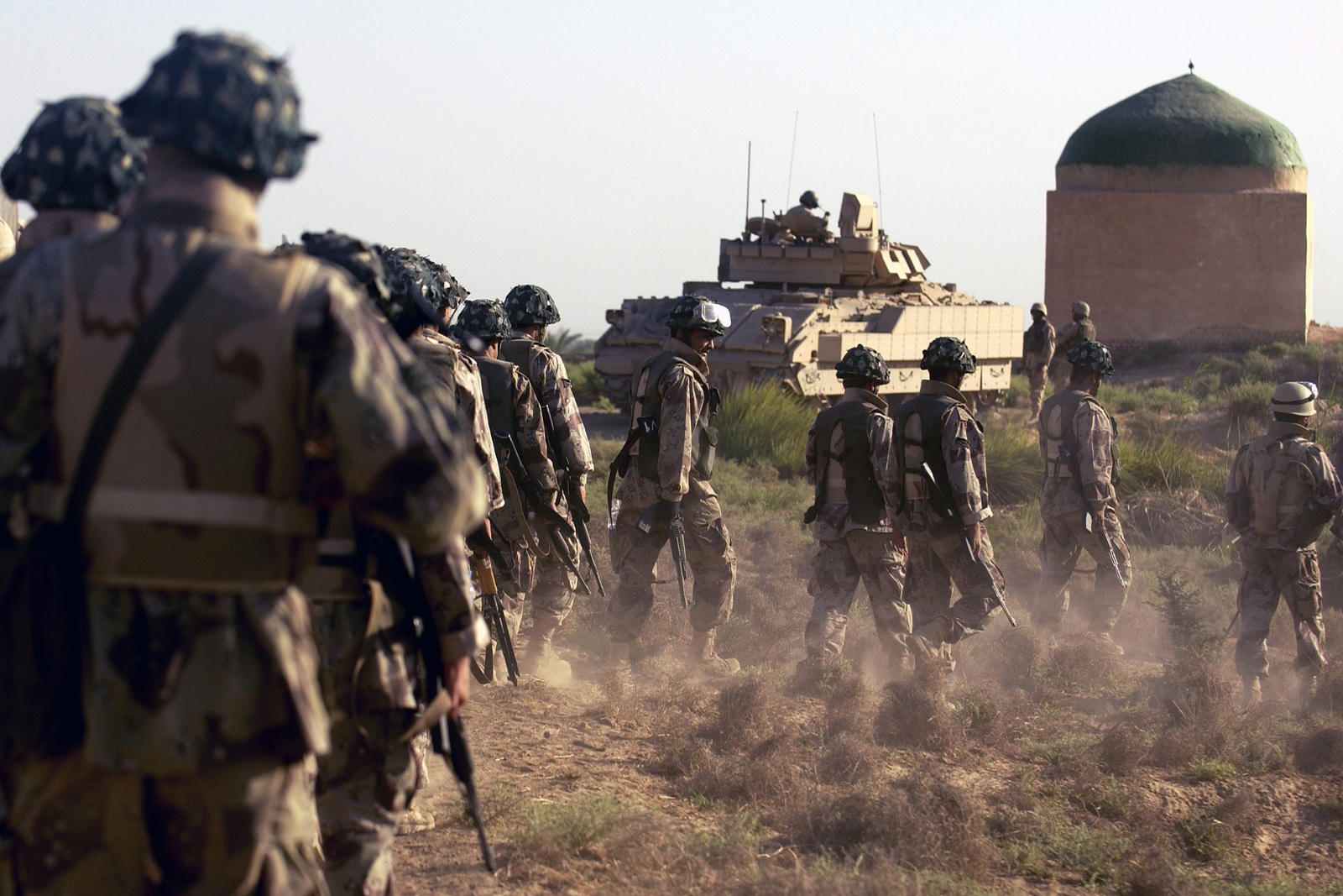 Iraqi Army (IA) 4th Battalion (BN), 1ST Brigade (BGDE), Iraqi Intervention Force (IIF), Soldiers and US Army Reserve (USAR) Soldiers walk a field patrol on the outskirts of the village of Al Taji, Baghdad Province, Iraq (IRQ), looking for a suspected mortar launch site during Operation IRAQI FREEDOM