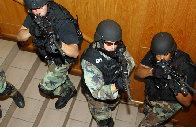 US Air Force (USAF) AIRMAN First Class (A1C) Eric Argenteri (left), USAF Captain (CPT) Steven Stone (center), and USAF STAFF Sergeant (SSGT) Timothy Stewart (right), all with the 52nd Security Forces Squadron (SFS) Emergency Services Team (EST), practice building clearing procedures during a training scenario on Spangdalem Air Base (AB), Rhineland-Pfalz, Germany (DEU)