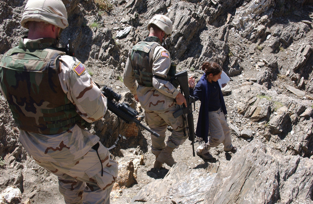 US Army (USA) Soldiers assigned to the 1/168th Infantry Battalion, armed with 5.56mm M16A2 rifles, escort a USA Agency International Developer from the Parwan Provincial Reconstruction Team (PRT), down a steep rocky hillside, to conduct a site assessment on a spring well, located in the Parwan Province of Afghanistan, during Operation ENDURING FREEDOM