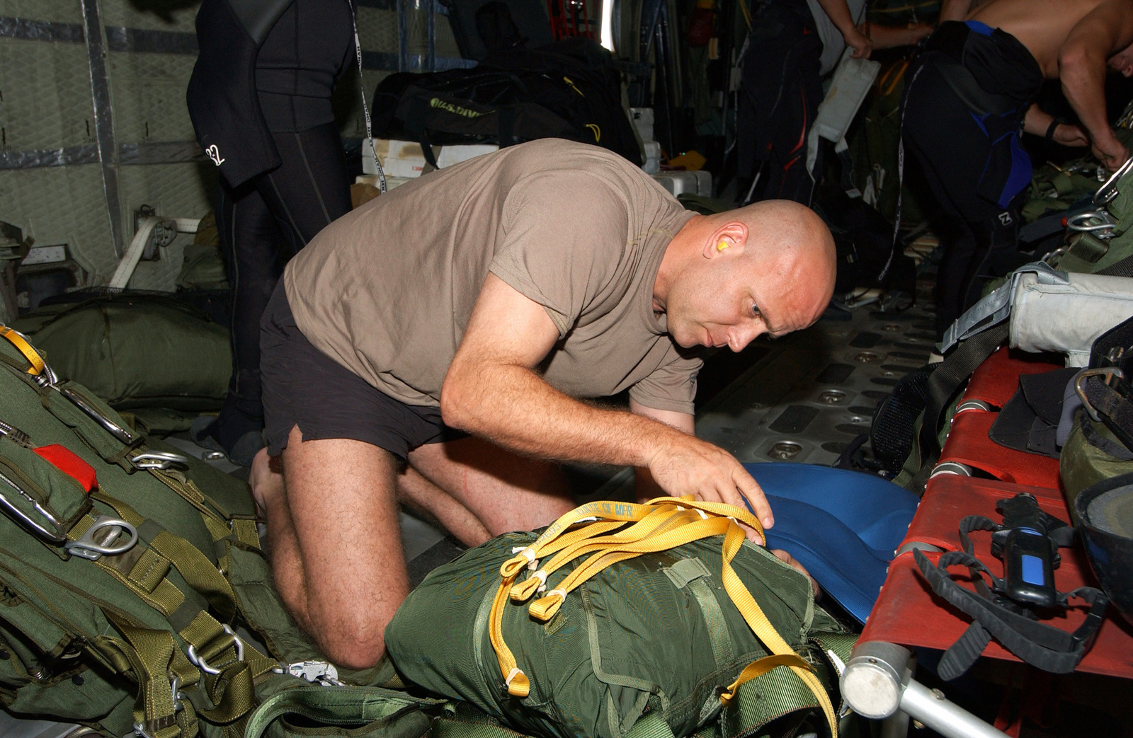 A US Air Force (USAF) 38th Rescue Squadron (RQS), 347th Rescue Wing (RW), Pararescueman, from Moody Air Force Base (AFB), Georgia (GA), prepares his gear while his Pararescue Team flies onboard a USAF C-130 Hercules cargo aircraft to provide medical support to a Chinese fisherman, aboard the fishing vessel the YUH PAO, who is suffering from a serious chest injury. Other team members are working in the background preparing the Rigging Alternate Method Zodiac (RAMZ) boat that will be dropped to deliver the pararescuemen to the YUH PAO