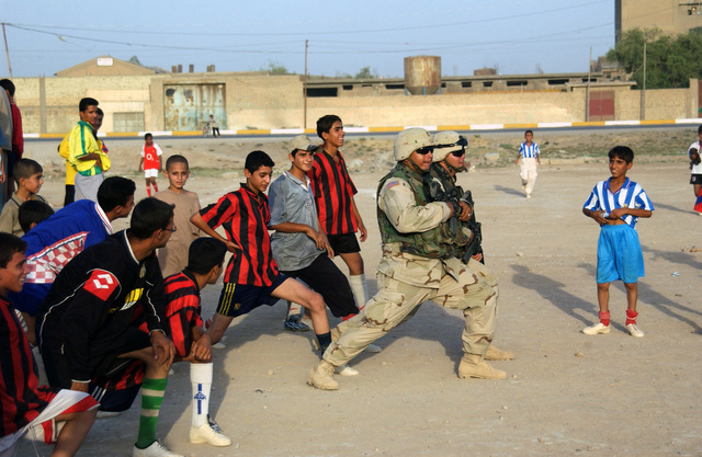 US Army (USA) SPECIALIST (SPC) Ramirez and STAFF Sergeant (SSG) Hernandez from the 478th Civil Affairs Battalion (CAB), play a game with a local soccer team in Baghdad