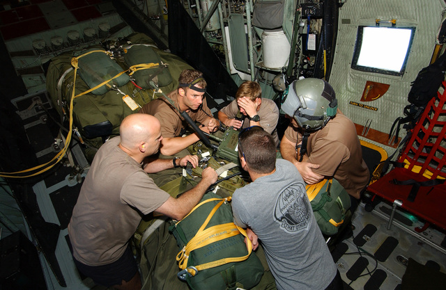 Five US Air Force (USAF) 38th Rescue Squadron (RQS), 347th Rescue Wing (RW), Pararescuemen, from Moody Air Force Base (AFB), Georgia (GA), review their mission plans, huddled around a Rigging Alternate Method Zodiac (RAMZ) boat, as they fly onboard a USAF HC-130P/N Hercules extended-range, combat search and rescue aircraft to provide medical support to a Chinese fisherman, aboard the fishing vessel the YUH PAO, who is suffering from a serious chest injury