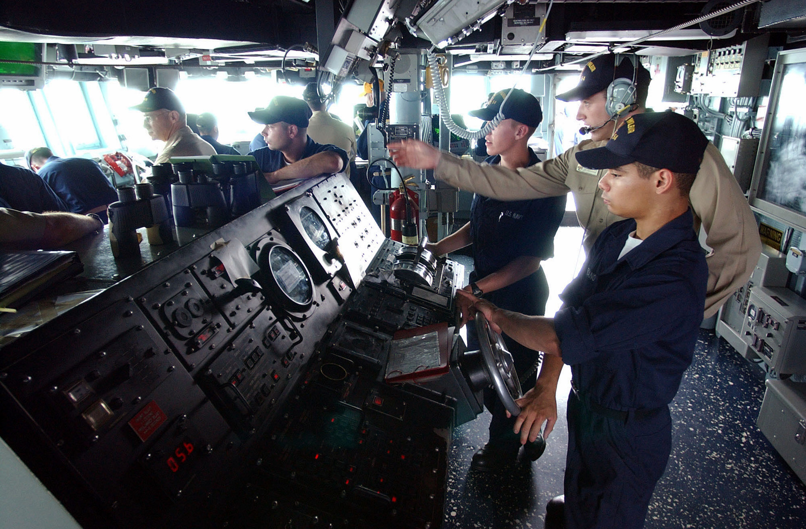 US Navy (USN) SEAMAN (SN) Edwin Laureano stands helmsman watch and executes rudder orders during sea and anchor detail on board the Yokosuka based USN Arleigh Burke Class Guided Missile Destroyer USS CURTIS WILBUR (DDG 54). The WILBUR, currently deployed in the 7th Fleet area of responsibility (AOR), undergoing testing and qualification by Afloat Training Group (ATG) and Commander, Destroyer Squadron 15, during the ships Mid-Cycle assessment