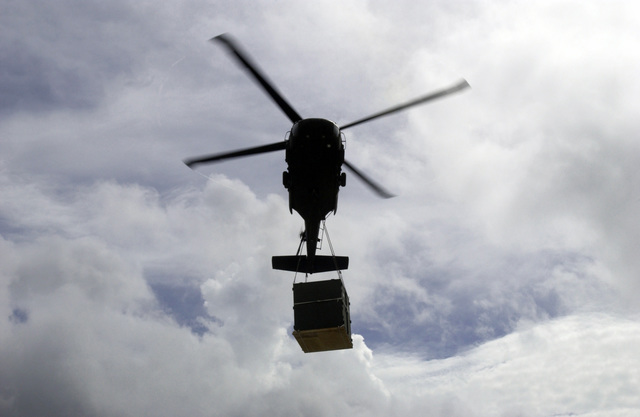 A Colorado Army National Guard (COARNG) 2nd Battalion (BN), 135th Aviation Regiment (2/135th) UH-60 Blackhawk (Black Hawk) utility helicopter flies overhead carrying a sling loaded Container Express (CONEX) pallet of medical supplies to be transported to New Amsterdam, Berbice District, Guyana (GUY), from Camp Stephenson, Timehri, East Bank Demerara (EBD) District, GUY, as part of a Operation NEW HORIZONS 2004. This operation is a four-month joint service training exercise being held in Guyana by elements of the US Southern Command (USSOUTHCOM) and the Guyana Defense Force (GDF), and it involves combined teams of US and GDF military personnel working on several construction projects and...
