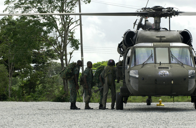 Guyana Defense Force (GDF) Soldiers board a Colorado Army National Guard (COARNG) 2nd Battalion (BN), 135th Aviation Regiment (2/135th) UH-60 Blackhawk (Black Hawk) utility helicopter to help guard medical supplies being transported to New Amsterdam, Berbice District, Guyana (GUY), from Camp Stephenson, Timehri, East Bank Demerara (EBD) District, GUY, as part of a Operation NEW HORIZONS 2004. This operation is a four-month joint service training exercise being held in Guyana by elements of the US Southern Command (USSOUTHCOM) and the Guyana Defense Force (GDF), and it involves combined teams of US and GDF military personnel working on several construction projects and two Medical...