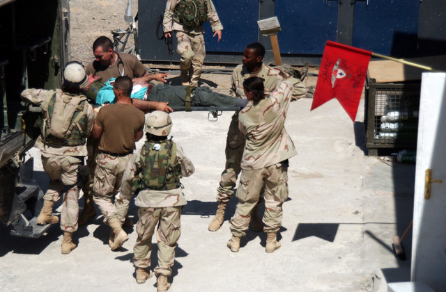 US Army (USA) soldiers with Task Force 1ST Battalion, 26th Infantry Medical Platoon, pull an injured civilian from a Forward Line Ambulance (FLA) after he was involved in a High Mobility Multi-purpose Wheeled Vehicle (HMMWV) rollover accident the Brassfield Mora main gate, in Samarra, Iraq, during Operation Iraqi Freedom