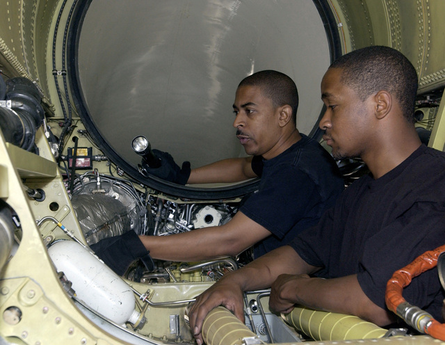 US Air Force (USAF) Technical Sergeant (TSGT) Gerald Jackson (left) and AIRMAN First Class (A1C) Dennis Lyons (right), both with the 31st Aircraft Maintenance Squadron (AMXS), inspect a training model of an F-16 jet engine during engine removal and installation training at the 31st AMXS training facility at Aviano Air Base (AB), Pordenone Province, Italy (ITA)