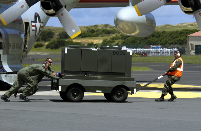 US Air Force (USAF) Technical Sergeant (TSGT) Mario de Souza (right), 65th Operational Support Squadron, and two LC-130H crew members (right) move an aircraft power unit (APU) away from The Pride of Scotia, a New York Air National Guard (NYANG) 139th Airlift Squadron (AS), 109th Airlift Wing (AW) LC-130H Hercules cargo aircraft with retractable ski-wheels, as it prepares to take off from Lajes Field, Azores (AZR), Portugal (PRT), on its way back to Stratton Air National Guard Base (ANGB)/Schenectady County Airport in Scotia, New York (NY), after participating in the 2004 Royal International Air Tattoo at RAF Fairford, England (ENG) where the aircrew won the prize for the best kept...