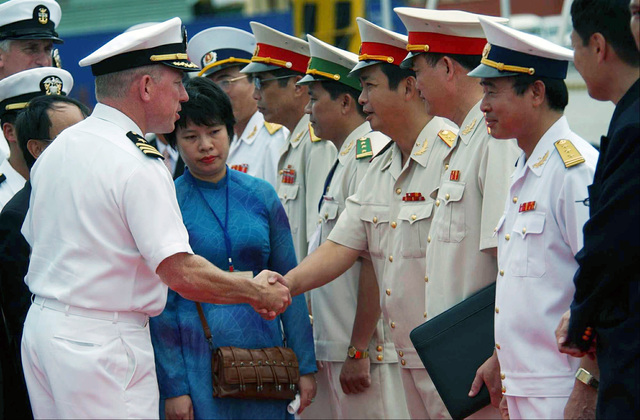 US Navy (USN) Commander (CDR) John T. Lauer III (left), Commanding Officer (CO), USS CURTIS WILBUR (DDG 54), greets members of the Vietnamese armed forces upon arrival in the city of Da Nang, Vietnam. The Arleigh Burke Class Guided Missile Destroyer is on scheduled port visit, the second USN ship to visit Vietnam and the first to visit Da Nang since 1973. These visits symbolize the continuation of normalized relations between the United States and Vietnam
