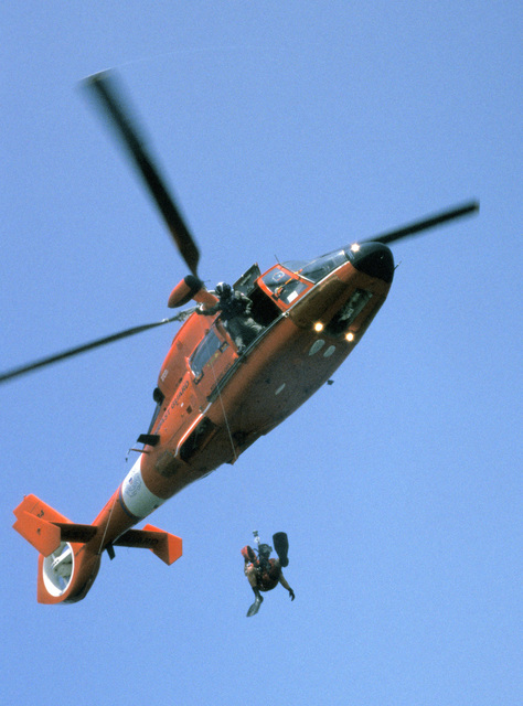 A US Coast Guard (USCG) HH-65C Dolphin short range recovery helicopter, from Coast Guard Air Station (CGAS) Atlantic City, New Jersey (NJ), District 5, Atlantic Area (LANTAREA), lowers USCG Aviation Survival Technician Third Class (AST3) Zee Lee to pick up US Air Force (USAF) air crew members, from McGuire Air Force Base (AFB), NJ, during water safety training certification as part of an overall water survival training program being conducted off the coast of Long Beach Island, NJ. (SUBSTANDARD)