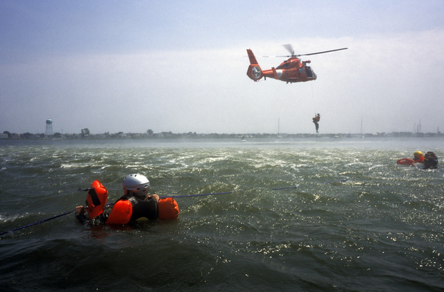 A US Coast Guard (USCG) HH-65C Dolphin short range recovery helicopter, from Coast Guard Air Station (CGAS) Atlantic City, New Jersey (NJ), District 5, Atlantic Area (LANTAREA), lowers USCG Aviation Survival Technician Third Class (AST3) Zee Lee to pick up US Air Force (USAF) air crew members, from McGuire Air Force Base (AFB), NJ, during water safety training certification as part of an overall water survival training program being conducted off the coast of Long Beach Island, NJ