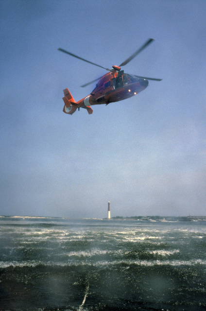 A US Coast Guard (USCG) HH-65C Dolphin short range recovery helicopter (in distance), from Coast Guard Air Station (CGAS) Atlantic City, New Jersey (NJ), District 5, Atlantic Area (LANTAREA), hovers over the ocean as it prepares to lower USCG Aviation Survival Technician Third Class (AST3) Zee Lee to pick up US Air Force (USAF) air crew members (not shown), from McGuire Air Force Base (AFB), NJ, during water safety training certification as part of an overall water survival training program being conducted off the coast of Long Beach Island, NJ. (SUBSTANDARD)