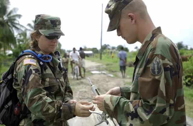US Army Reserve (USAR) Captain (CPT) Melinda Hutton (left) and Sergeant (SGT) Joseph Thomas (right), 109th Medical Detachment Veterinary Services (MDVS), 63rd Reserve Readiness Command (RRC), replace a needle in an auto-injector while conducting a Veterinarian Readiness Exercise (VETRETE) in Anna Regina, Pomeroon-Supenaam Region, Guyana (GUY), as part of a Operation NEW HORIZONS 2004. This operation is a four-month joint service training exercise being held in Guyana by elements of the US Southern Command (USSOUTHCOM) and the Guyana Defense Force (GDF), and it involves combined teams of US and GDF military personnel working on several construction projects and two Medical Readiness...