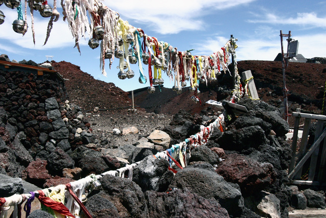 Once a hiker reaches the summit, they leave the bells attached to their hiking stick at the top of Mt. Fuji, Japan