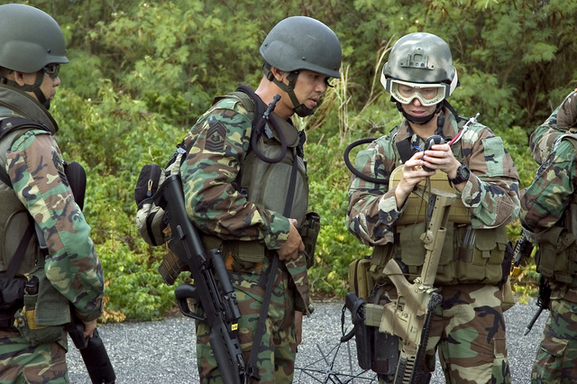 US Navy (USN) Operation SPECIALIST 2nd Class (OS2) Jody Heflin, Detachment 53 (Det.53), Explosive Ordnance Disposal Mobile Unit 5 (EODMU-5), instructs Republic of Singapore Navy (RSN) Sailors in the proper use of a global positioning unit during Exercise TRI-CRAB 2006, onboard USN Santa Rita Naval Base (NB), Guam (GUM). TRI-CRAB 2006 is an annual multi-national explosive exercise designed to increase the interoperability skills of USN, RSN, and Royal Australian Navy (RAN) EOD technicians in a friendly, forward-deployed environment