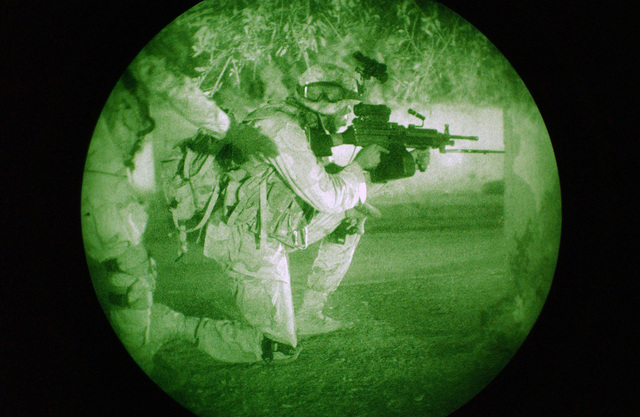 A night vision goggle view early in the morning of U.S. Army SPC. Williams from Charlie Battery, 1ST Battalion, 7th Field Artillery Regiment, 1ST Infantry Division (ID), is given the signal to move, during a night patrol.  He aims his FNMI 5.56mm M249 Squad Automatic Weapon (SAW) on one knee. (U.S. Army PHOTO by PFC Elizabeth Erste) (Released)