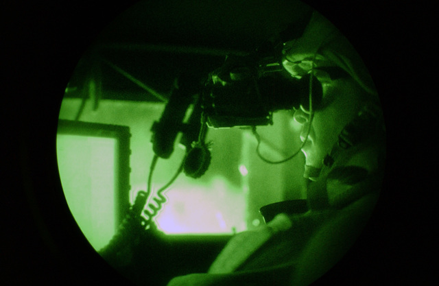 A night vision goggle view early in the morning of U.S. Army 1ST SGT. Michael Grinston, from Charlie Battery, 1ST Battalion, 7th Field Artillery Regiment, 1ST Infantry Division (ID).  Sergeant Grinston monitors his position on the Global Postioning System (GPS) during a night patrol.is given the signal to move, during a night patrol.  He aims his FNMI 5.56mm M249 Squad Automatic Weapon (SAW) on one knee. (U.S. Army PHOTO by PFC Elizabeth Erste) (Released)