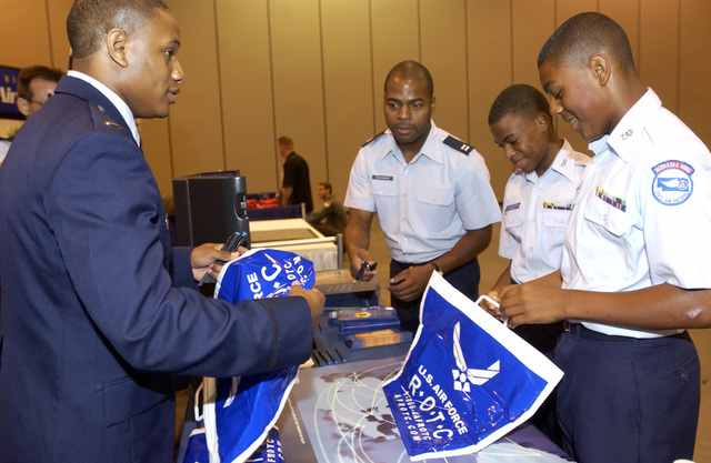 Civil Air Patrol (CAP) US Air Force (USAF) MASTER Sergeant (MSGT) Michael Thomas and MSGT Dwayne Roger (right), with the 99th Nebraska (NB) Wing accept recruitng information from the Tuskegee University personnel during the Tuskegee Airmen, 33rd Annual National Convention, held at the Hilton, Qwest Convention Center Omaha, Nebraska (NB)