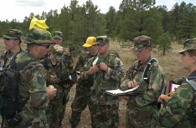 US Air Force (USAF) Technical Sergeant (TSGT) Juan Toledo (right), with the 56th Operations Support Squadron (OSS) Non-Commissioned Officer In Charge (NCOIC) critiques Air Force Junior Reserves Officer Training Corps (JROTC) Cadets while they work on navigation skills during Summer Leadership School at Camp Navajo, near Flagstaff, Arizona (AZ)