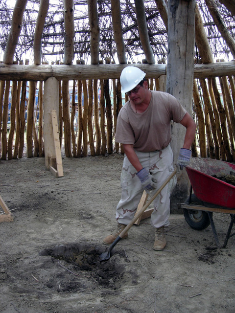 U.S. Army SPEC. Lyle Lumbar, North Dakota National Guard (NDANG), digs a whole in the center of an earth lodge on Aug. 4, 2004 at Fraine Barracks, North Dakota, to be used as a fire pit and the only source of heat during part of the Innovative Readiness Training (IRT) program.  An earth lodge is part of an authentic Mandan Indian cultural display being constructed during the Lewis and Clark Bicentennial events.  (U.S. Army photo by STAFF SGT. Billie Jo Lorius) (Released)