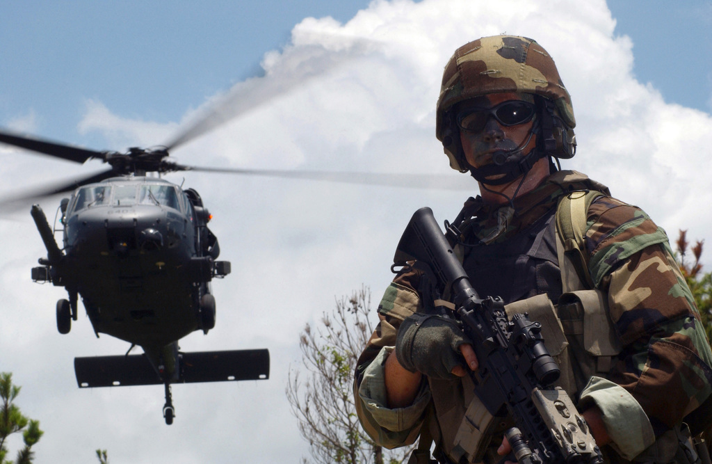 Standing at the ready as a US Air Force (USAF) UH-60 Black Hawk (Blackhawk) helicopter lands, Sergeant (SGT) William Moore with the 31st Rescue Squadron (RS), a Pararescueman, helps secure a landing zone in the jungles of Okinawa, Japan (JPN), while training in support of the Global War on Terror