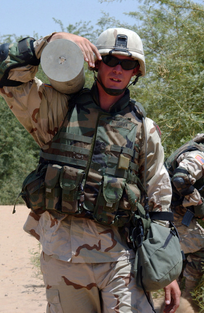 U.S. Army SGT. O'Brien, , Alpha Battery, 1ST Battlion, 7th Field Artillery Regiment, 1ST Infantry Division, carries captured artillery shell found in a field outside Bayji, Salah al-Dein, Iraq, on Aug. 5, 2004, in support of Operation Iraqi Freedom.  (U.S. Army photo by PVT. 1ST Class Elizabeth Erste) (Released)