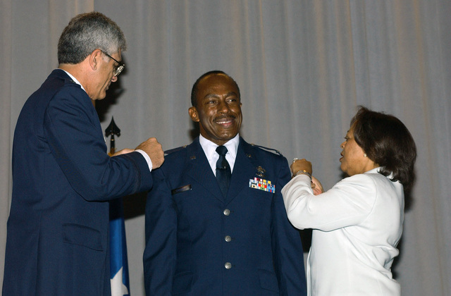 US Air Force (USAF) Colonel (COL) Edward F. Crowell, Commander of the Second Air Force Mobilization Group, Keesler Air Force Base (AFB), Mississippi (MS), is promoted to Brigadier General (BGEN) by Lieutenant General (LGEN) John Regni, Air University Commander at Maxwell AFB, Alabama (AL). Mrs. Crowell helped during the ceremony held at the Maxwell Officers Club