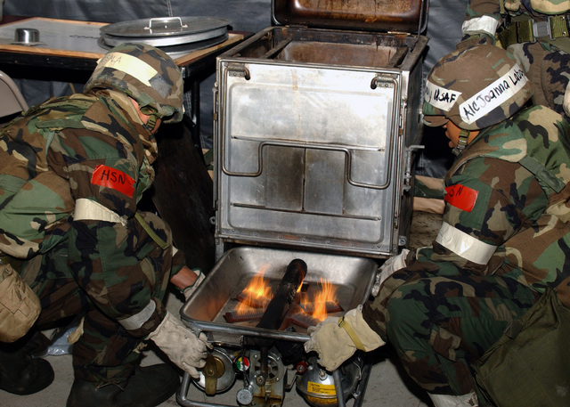 US Air Force (USAF) Airmen 1ST Class (A1C) Micah Sala and A1C Joanna Laboy, with the 5th Services Squadron (SS), light and install M2A burning units into a stove used to warm food during a base exercise at Minot Air Force Base (AFB), North Dakota (ND)
