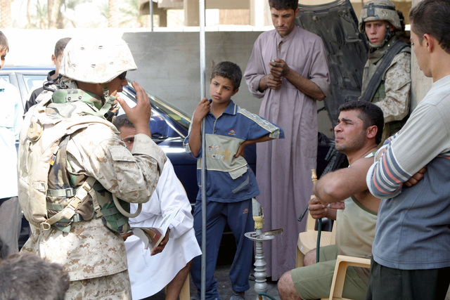 An Iraqi civilian interpreter, with the US Marine Corps (USMC) 4th Civil Affairs Group (CAG), 1ST Marine Division (MARDIV), explains to an Iraqi civilian why his home is being searched for illegal contraband, weapons, and propaganda. The 4th CAG is involved in a Security and Stabilization Operation (SASO) in Al Habbaniyah, Al Anbar Province, Iraq, during Operation IRAQI FREEDOM