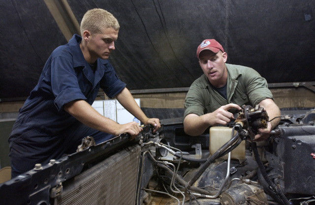 US Air Force (USAF) STAFF Sergeant (SSGT) Gavin Trzepacz (right) and AIRMAN 1ST Class (A1C) Michael Harris members of the 820th Red Horse Squadron (RHS) at Nellis Air Force Base (AFB), Nevada (NV), install an engine at Camp Stevenson. New Horizons 2004-Guyana is a joint service training exercise held in Guyana (GUY)
