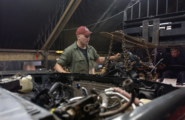 US Air Force (USAF) STAFF Sergeant (SSGT) Gavin Trzepacz with the 820th Red Horse Squadron (RHS) at Nellis Air Force Base (AFB), Nevada (NV), installs an engine at Camp Stevenson, Guyana (GUY). New Horizons 2004-Guyana is a joint service training exercise held in Guyana