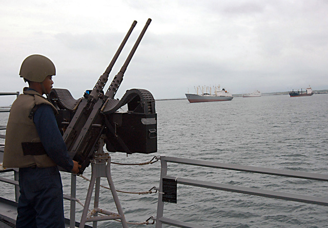 US Navy (USN) Gunners Mate 3rd Class Ali Cowden ms the twin .50-caliber Browning Machine gun as the Oliver Hazard Perry Class Guided Missile Frigate USS CROMMELIN (FFG 37) pulls out of Colon, Pama, to participate in the maritime portion of PANAMAX 2004. CROMMELIN, along with Naval forces from eight countries, is participating in PANAMAX 2004, a naval exercise designed to build up a coalition response to security threats against the Pama Cal. PANAMAX, conducted under the direction of Commder Naval Forces Southern Commd, involves the identification, monitoring d interdiction of vessels posing a simulated terrorist threat to the Cal. The multinational force includes surface...