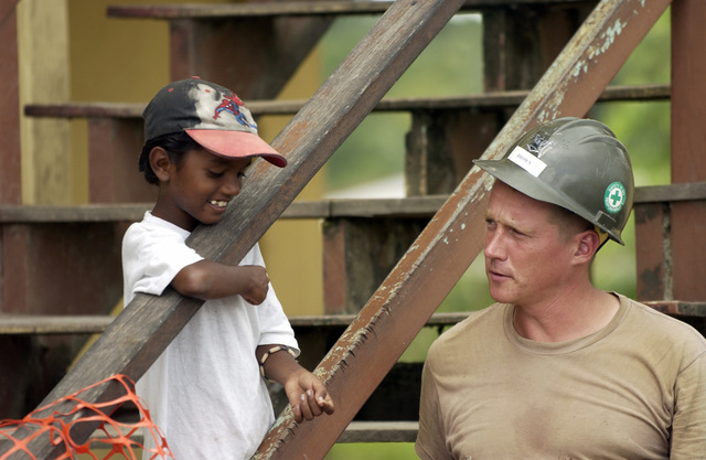 US Navy (USN) PETTY officer Third Class (PO3) Ronald Brown, assigned to Navel Mobile Construction Battalion 3 (NMCB-3), interacts with a local child, during a construction project at the Timehri School, in Guyana, during Exercise New Horizons 2004-Guyana. The Exercise is a joint service training exercise held in Guyana, South America co-sponsored by the US Southern Command (USSOUTHCOM) and the Guyana Defense Force (GDF)