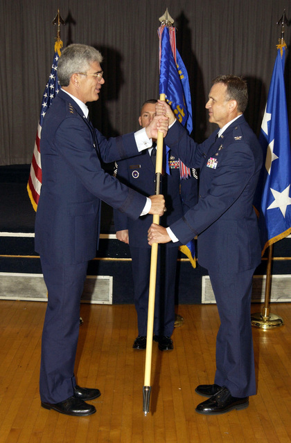 US Air Force (USAF) Colonel (COL) Howard Short (right) accepts command of Ira Eaker College for professional development from USAF Lieutenant General (LGEN) John Regni, Commander, Air University in the ballroom at the Officer's Club at Maxwell Air Force Base (AFB), Alabama (AL)