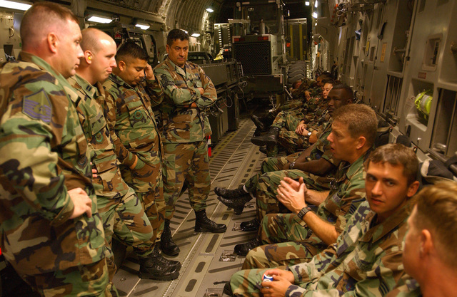 US Air Force (USAF) Airmen from the 621-8 tanker airlift control element (TALCE), McGuire Air Force Base (AFB), New Jersey (NJ), discuss their upcoming mission, to provide airlift support for Hurricane Charley relief efforts, while on board a USAF C-17A Globemaster III cargo aircraft in route to Lakeland, Florida (FL). Lakeland Regional Airfield is the center of relief operations in Florida for the Federal Emergency Management Agency (FEMA). The USAF is providing support by transporting tons of equipment, personnel, and supplies via air, expediting the delivery of the much needed supplies
