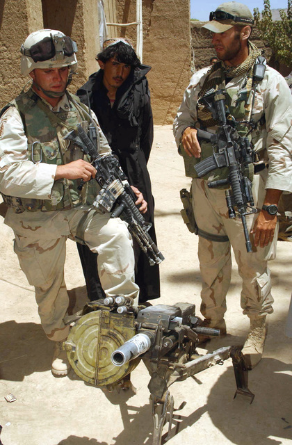 US Army (USA) STAFF Sergeant (SSG) John Lloyd (left, and Captain (CPT) Robert Matthews (right), both assigned to the 2nd Embedded Training Team, (ETT), B/Company, 2-5 Infantry, examine an Iraqi 30mm AGS-17 Automatic Grenade Launcher found in a house in the village of Kachari, Afghanistan, while conducting a village assessment, during Operation ENDURING FREEDOM. Both Soldiers are armed with 5.56mm M4A1 Modular Weapons System (MWS) equipped with the Knight Armament Company (KAC), Rail Interface System (RIS)