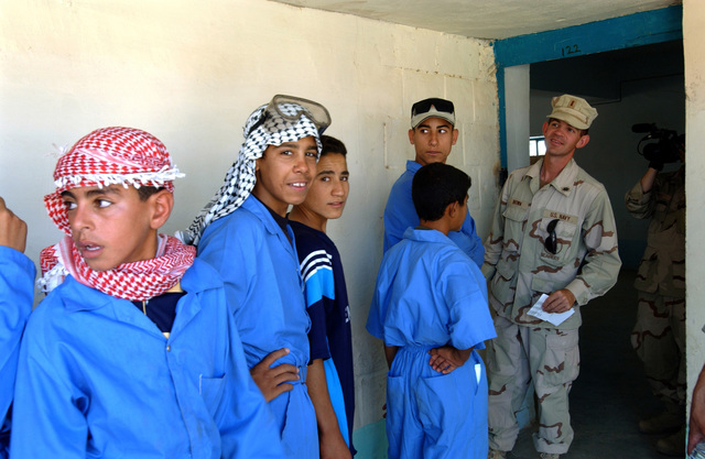 040818-F-4441R-054 (Aug. 18, 2004)US Navy (USN) ENSIGN Michael Brown, Officer In Charge (OIC), Iraqi Construction Apprentice Program (ICAP) lines up the ICAP students so he can pay them their weekly salary in Ar Ramadi, Al Anbar, Iraq (IRQ), during Operation IRAQI FREEDOM.  U.S. Air Force PHOTO by SENIOR AIRMAN Jorge A. Rodriguez (RELEASED)